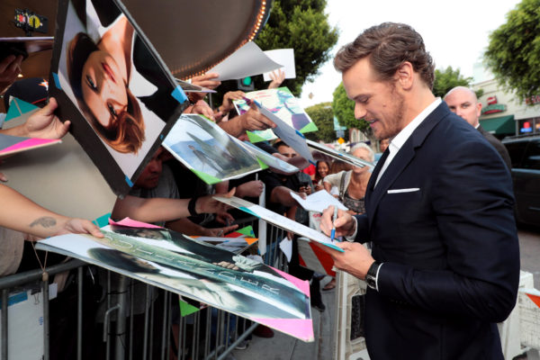 Sam Heughan signs autographs at the premiere.